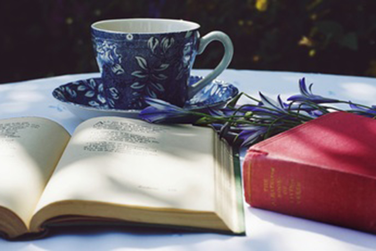 An open book in front of a teacup.