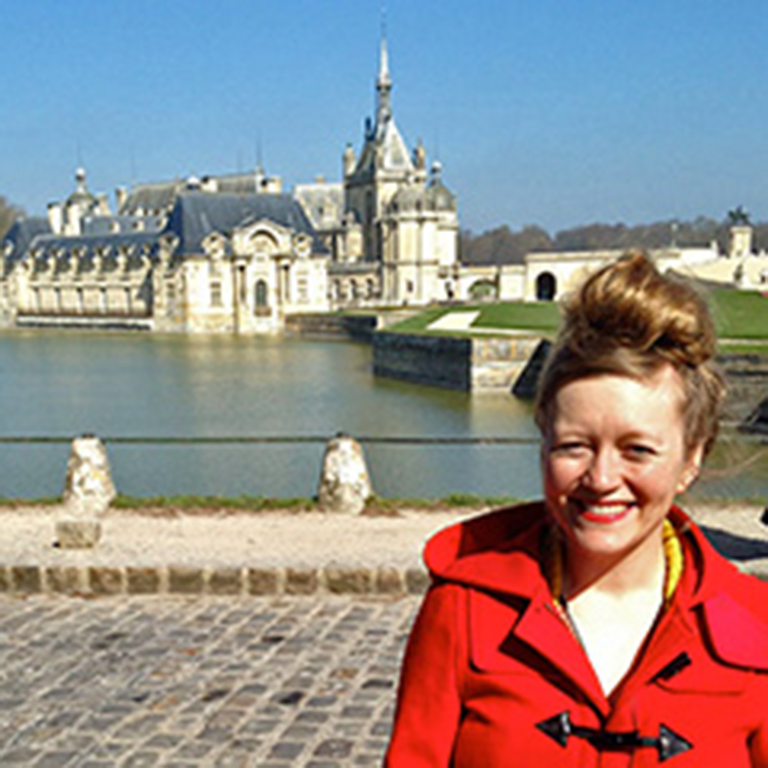 Kate Bastin outside the gate of the Château de Chantilly.