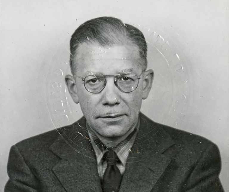 Francis Gravit, 1960 passport photo. The distortion in the image comes from the blindstamp impressed on the image. Courtesy the IU Archives.